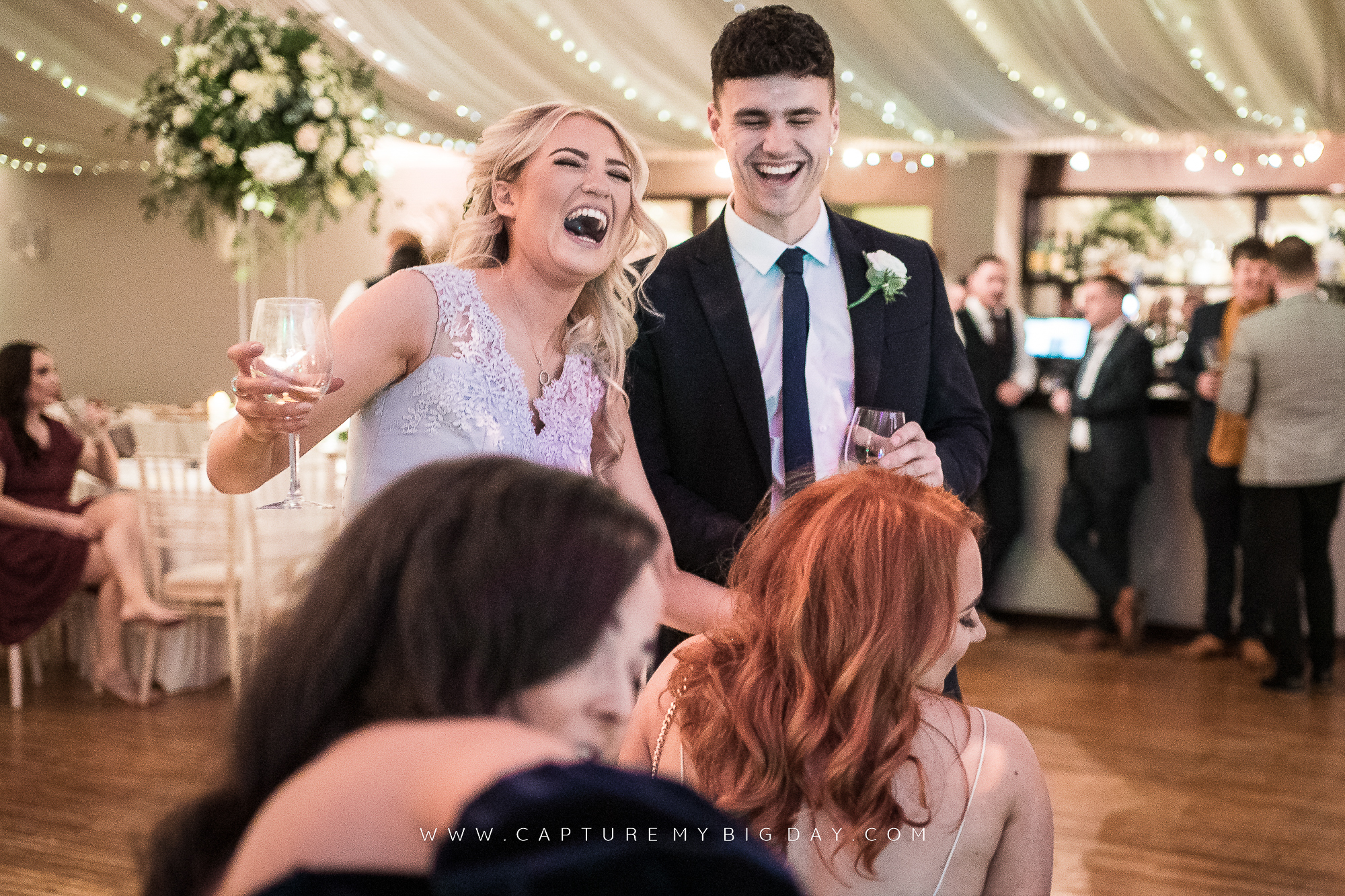 evening wedding guest laughing