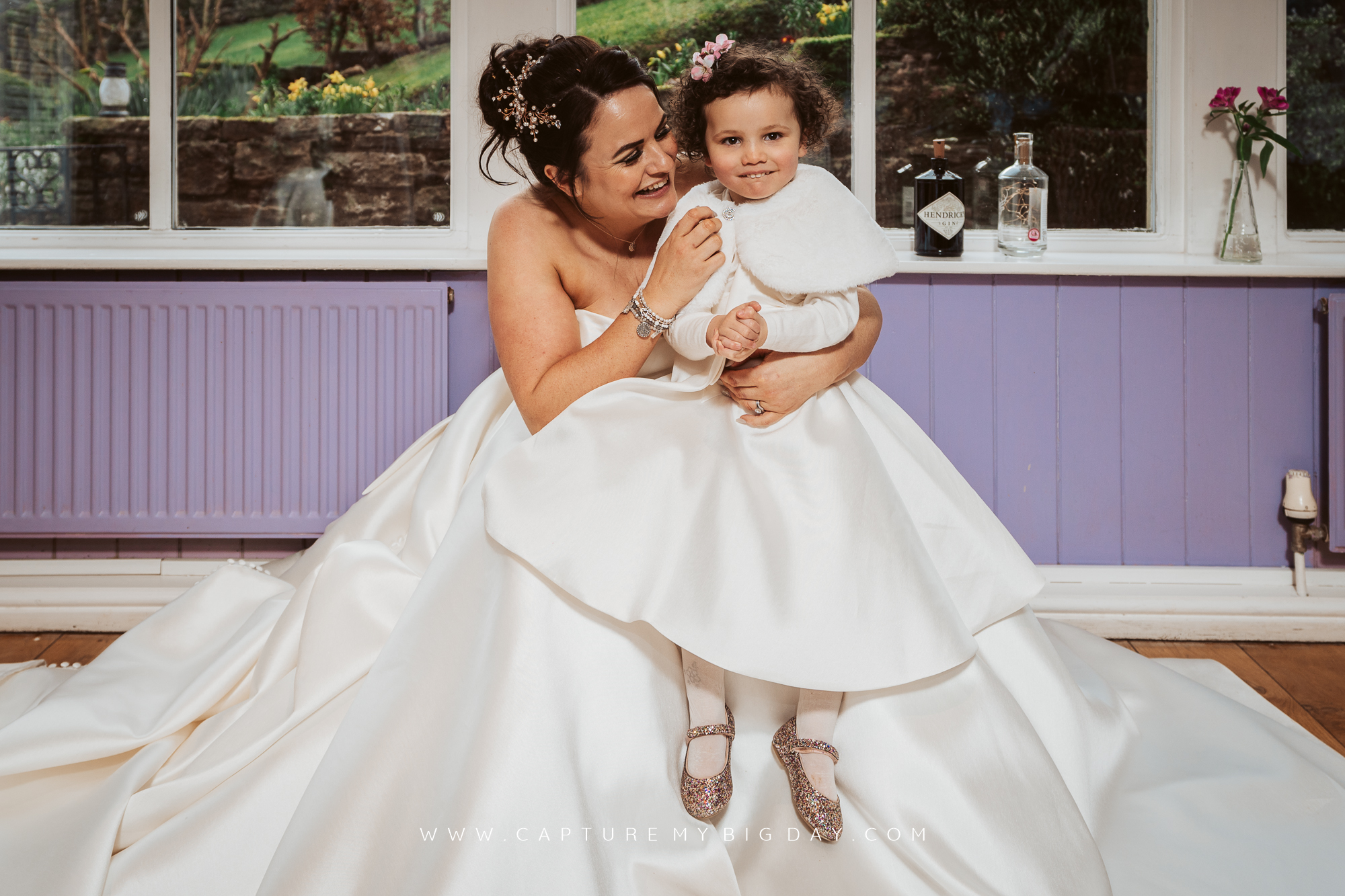 flower girl sitting on bride with white dress
