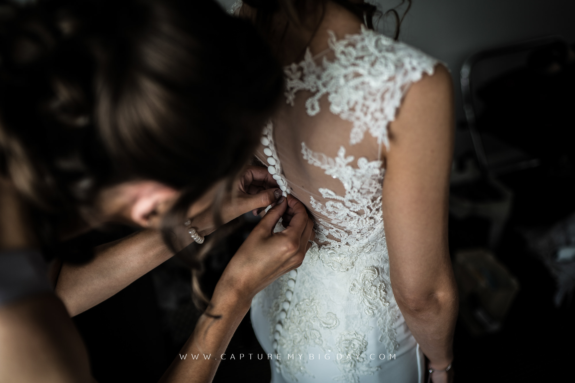 wedding dress being buttoned up
