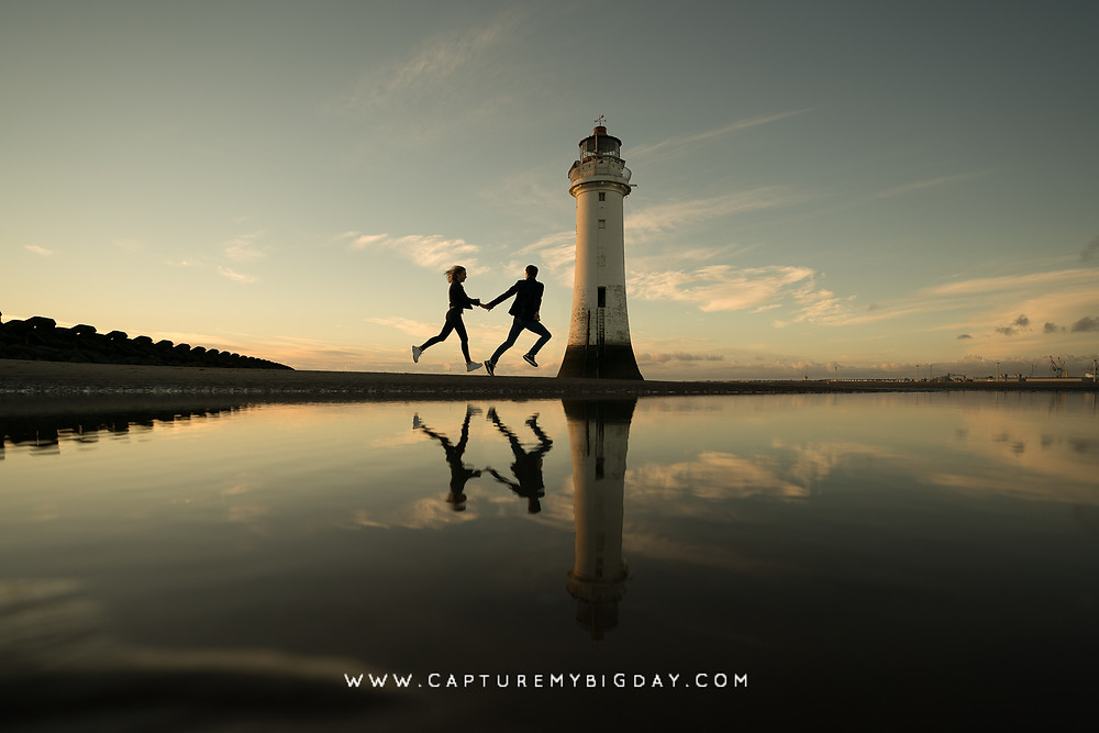 couple running past lighthouse