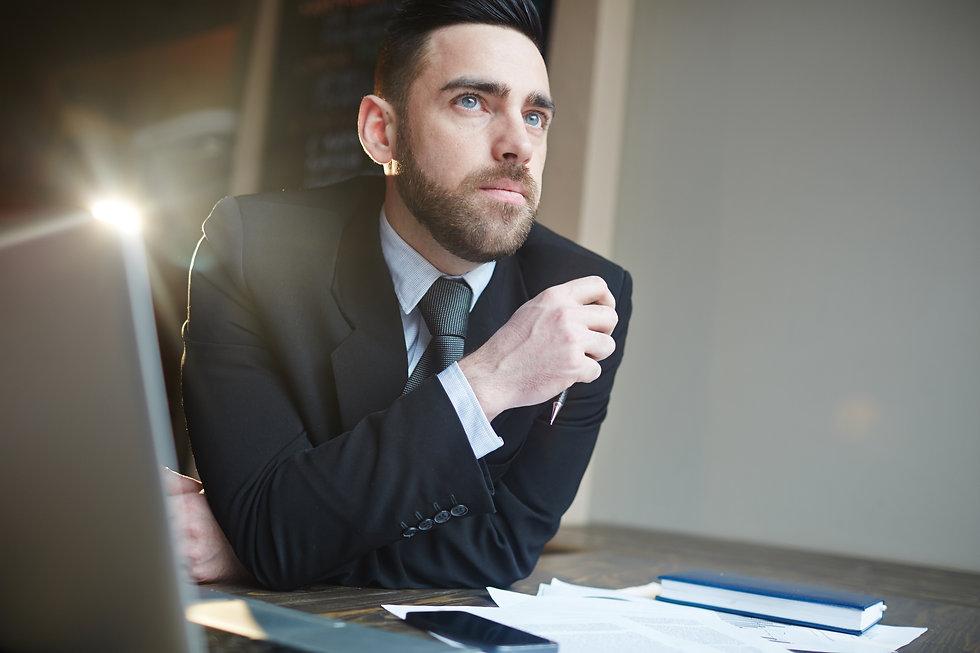 Portrait-of-businessman-thinking-at-desk