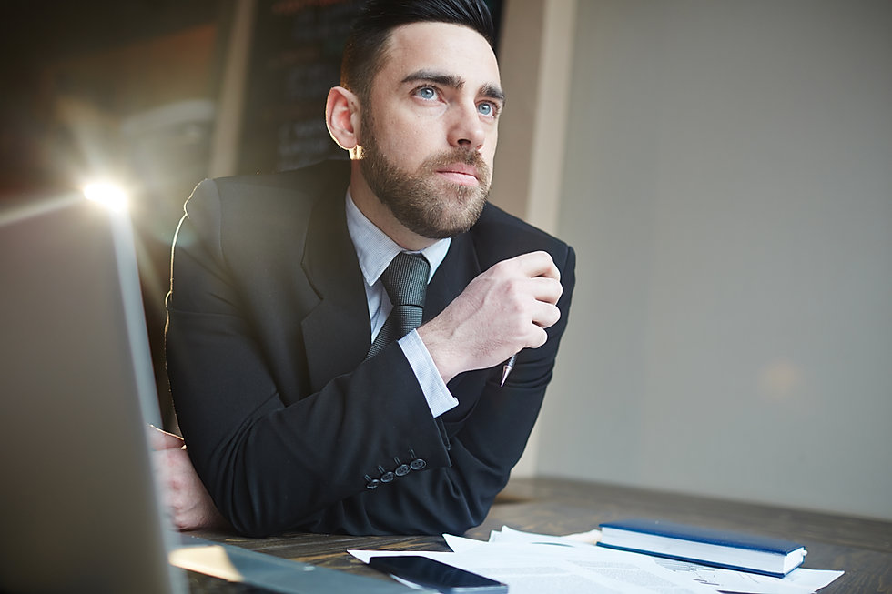 Portrait-of-businessman-thinking-at-desk