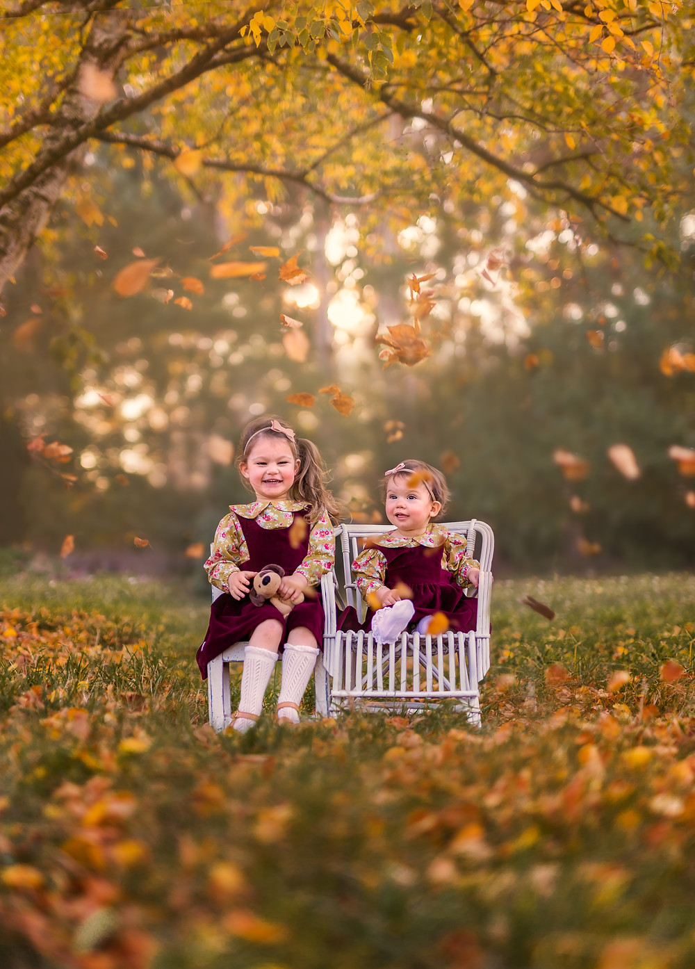 Two little girls being showered with leaves