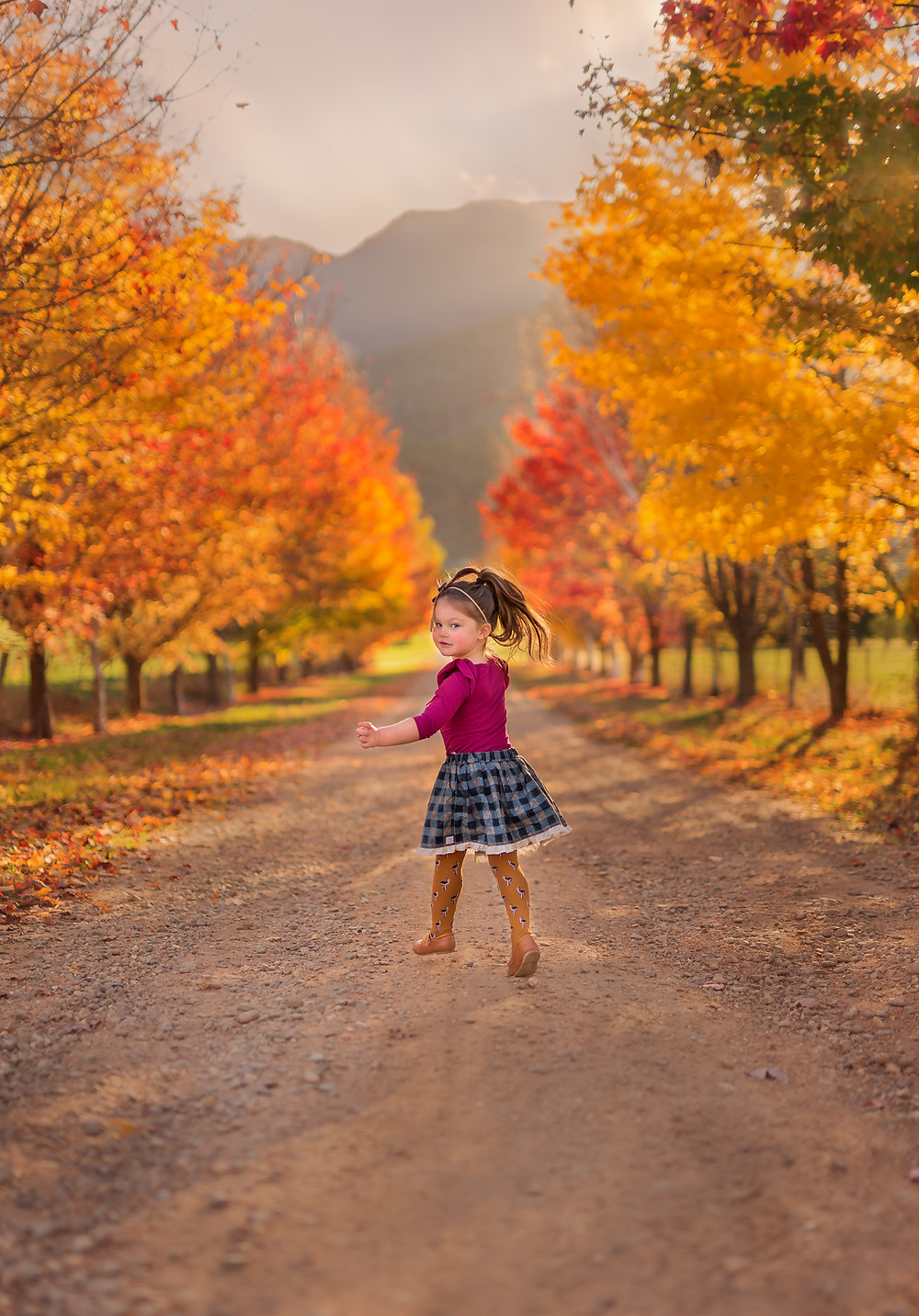 Little girl running down a road lined with vibrant Autumn trees