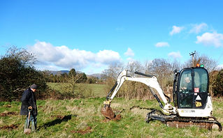 Digger making holes for tree planting
