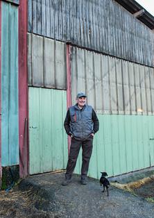 Robert devant le batiment principal de la ferme, accompagné de Kikinou, le plus petit des chiens mais selon lui, le plus malin.