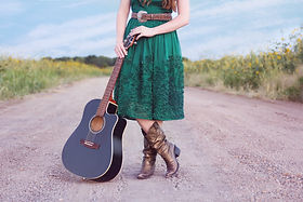 Dress from waist down with boots. standing on dirt road with guitar