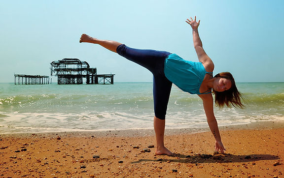 Yoga teacher xenia is practicing yoga at Brighton beach in front of the old pier