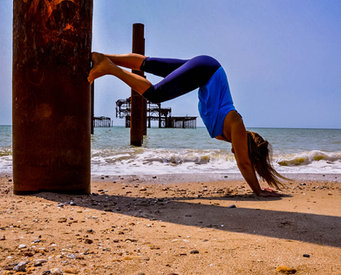 Fun on the beach yoga practicing handstands at Brighton beach