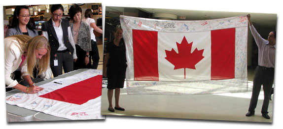 People at Commerce Court signing the fabric around the perimeter of the Canada Flag.