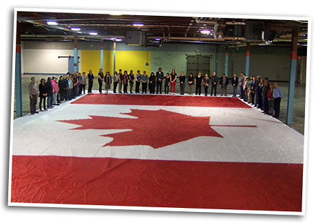 A gigantic Canada flag made by Flags Unlimited laid out with our staff for size perspective.