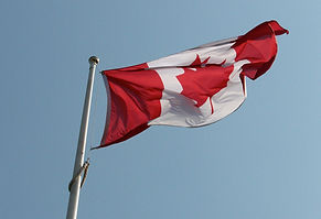 A giant Canadian applique flag flying from pole.