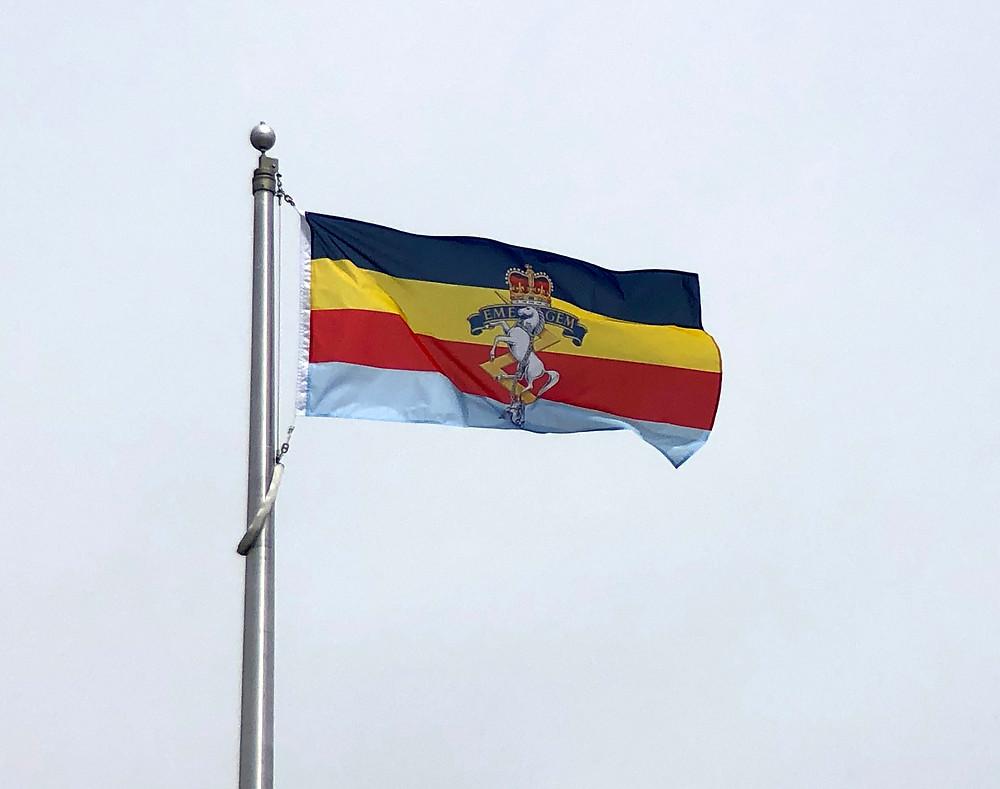 75th Anniversary RCEME flag flying on flagpole.