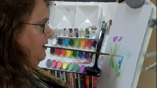 Nancy Hall working on an image of purple and blue flowers.  Her paint kit featured promonently in the back.  Nancy has a paint brush in her mouth and is adding a stroke to her painting.