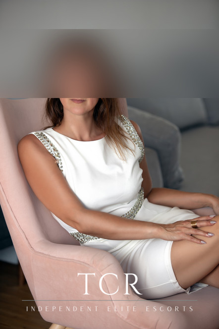 Smiling woman with brown hair sitting in pink chair wearing white dress