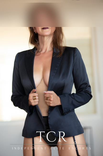 Confident brunette woman posing with suit and luxury lingerie