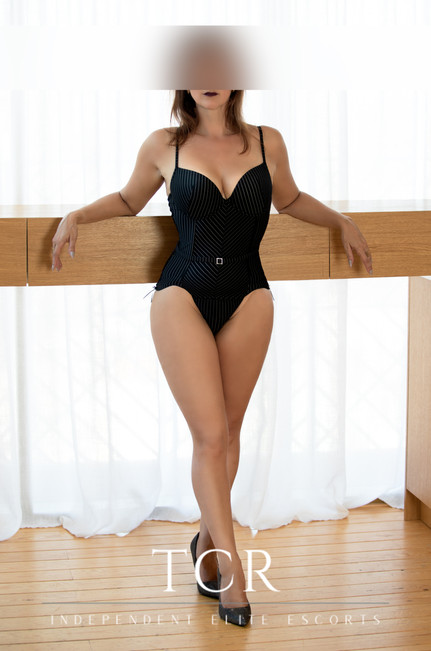 Curvy escort posing in beautiful black corset in front of white curtains