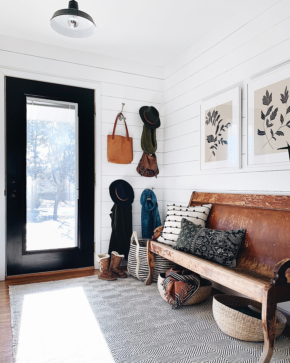shiplap foyer with black door and wall hooks