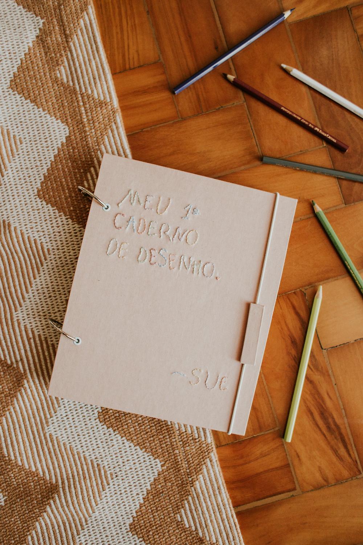 """Caderno de desenho rosa clarinho com bordado """"Meu primeiro caderno de desenho"""" posicionado no chão com lápis de cor espalhado ao redor."""