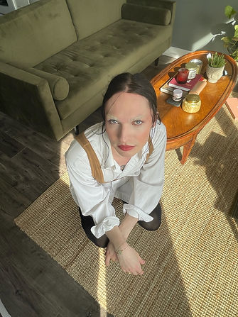 Image of a non-binary person crouched down, looking up to the camera wearing a white long sleeve button-up and black tights