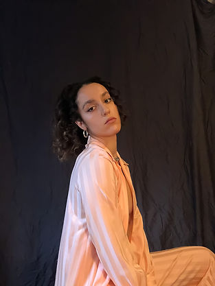Image of woman sitting, looking into the camera wearing a striped pink silk pajama-style outfit in front of a black sheet background
