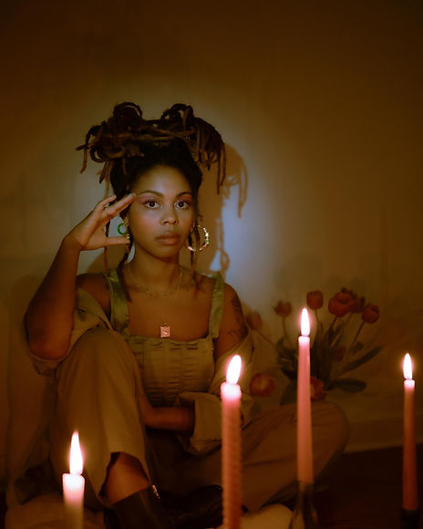 Image of shn shn sitting in a candle-lit room surrounded by candles and pink tulips
