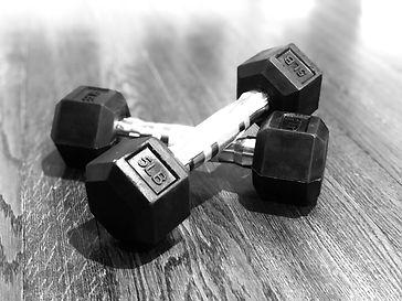 Black and white 5 pound dumbbells on hardwood floor