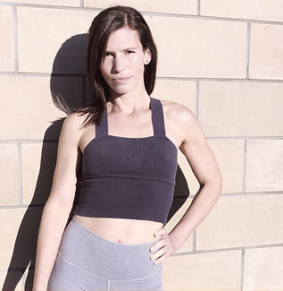 Headshot of Allyson Joy, standing outside against light brick wall