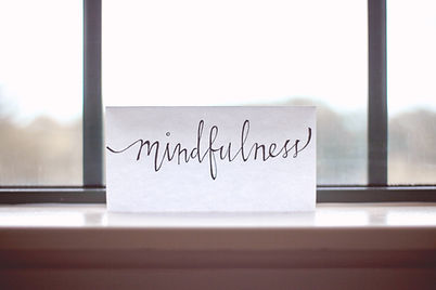 """White card with """"mindfulness"""" written in script, sitting atop windowsill"""
