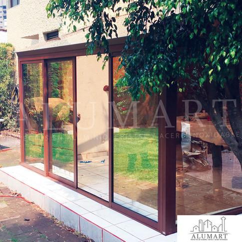 Ventanal en alumionio tono madera nogal con cristal en 6mm sol-lite