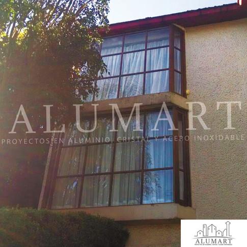 ventana en aluminio tono madera con cuadricula tipo californiano con cristal claro en 6mm