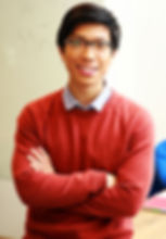 HireIO tech recruitment services, photo of asian man with glasses and red jumper standing with arms folded