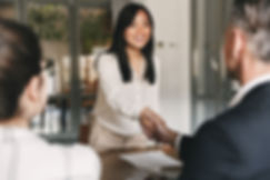 HireIO tech recruitment services, photo of asian woman shaking hands with office worker