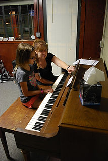 Angelica teaching a group of children about the piano