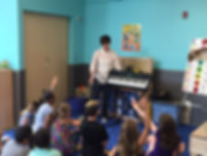 Angelica teaching a group of children from Stow and Hudson about the piano!