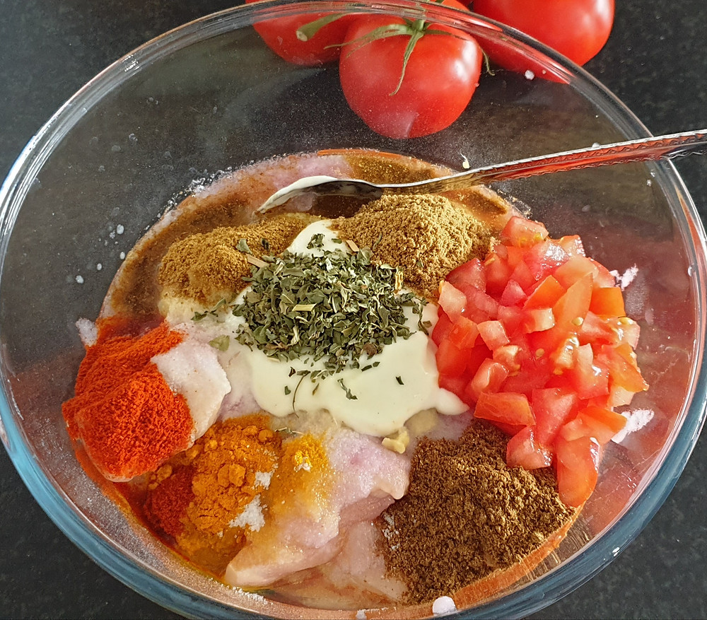 Marinating chicken with yogurt and spices.