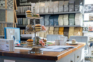 Inviting image of MTM's consultation table, adorned with cakes and tiling information & accessories.