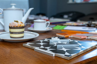 Close-up of tile and grout sample combinations on consultation table with cake and tea