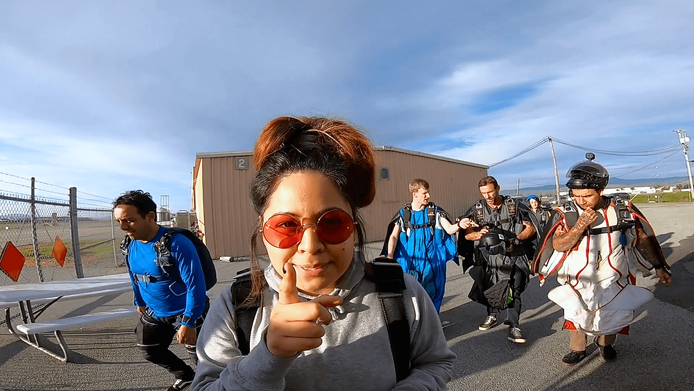 Lindsey points at the camera while walking to the plane, ready for her first skydive.