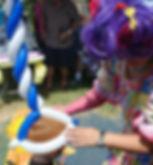 Cutie Pie putting balloon hat on child