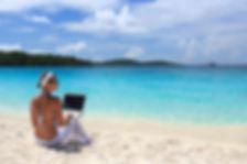 Lady-In-White-w-Laptop-On-Beach-Fotolia_