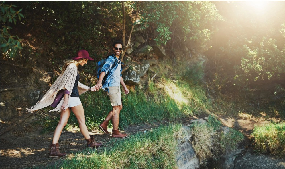 Happy couple who walk in nature to lower anxiety and high blood pressure by exercise