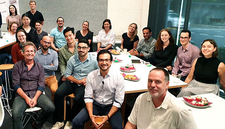Office workers sitting around a meeting table facing camera   The Open Mind Institute