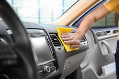 Man cleaning car dashboard with rag, clo