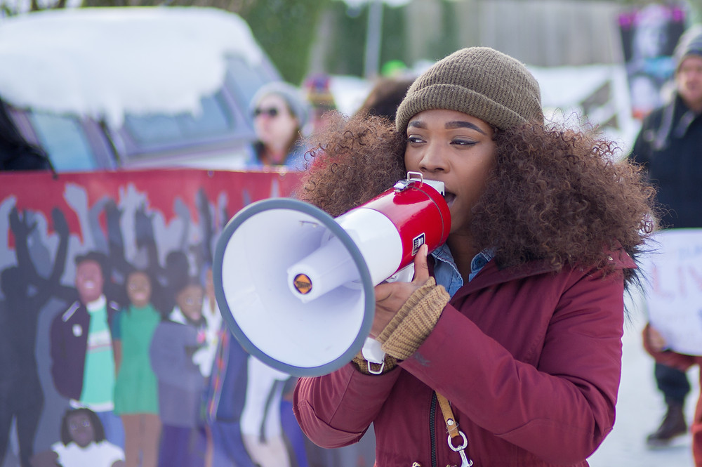 [Photo of a young woman speaking intoa megaphone at a protest.] Editorial credit:Diego G Diaz/Shutterstock.com