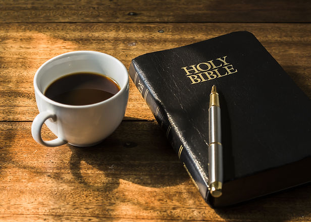 the holy bible with pen and a cup of coffee against widow light, focus on word Holy bible