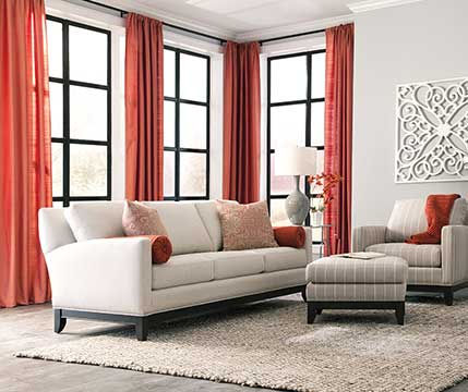 A photograph of a bright contemporary lving room with sofa, chair, ottoman and red curtains surrounding sunny windows.
