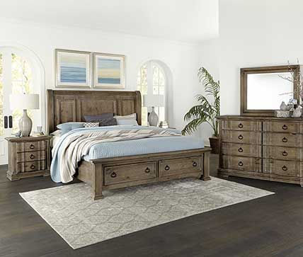 A photograph of a rustic bedroom suite, headboard, footboard, dresser, mirror and nightstand in a white room with a sunny widow.