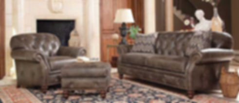 A photograph of a brown leather sofa, chair and ottoman in a living room with a fireplace and area rug.