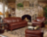 A Smith Brothers furniture brown leather sofa, chair and ottoman in a rustic room setting with stone fireplace and rug